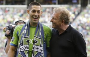 Clint Dempsey, left, captain of the U.S. National Soccer Team, is introduced as the newest member of the Seattle Sounders FC MLS soccer team by majority owner Joe Roth, right, Saturday, Aug. 3, 2013, prior to a match between the Sounders and FC Dallas in Seattle.