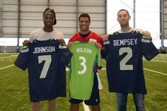 Eddie Johnson (left), formerly of the Seattle Sounders, Russell Wilson (middle) QB of the Seattle Seahawks, and Clint Demsey (right), current captain of the  Sounders all pictured together.