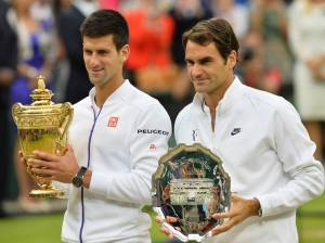 Novak Djokovic (left) and Roger Federer (right) lift the champion and runner-up trophies on Sunday, July 12th at the All-England Club.
